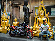 09 MARCH 2016 - BANGKOK, THAILAND:  A man reads a newspaper in front of statues of the Buddha on Thanon Bamrung Muang in Bangkok. The street is lined with workshops that make statues of the Buddha and revered Thai Buddhist monks. Once located just outside Bangkok's city walls, it's now in the heart of the city.     PHOTO BY JACK KURTZ