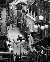People walking in historic streets Rue du Petit Champlain and Rue Sous Le Fort of old Quebec City in the evening, view from above. Quebec, Canada. Black and white photo. Rue du Petit-Champlain, Ville de Québec.