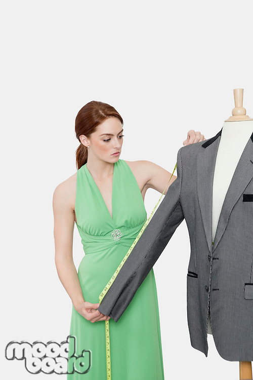 Female tailor measuring sleeve of suit over gray background
