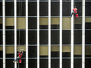 """07 APRIL 2020 - DES MOINES, IOWA: Window washers work on the Financial Building, an office tower on Walnut Street in downtown Des Moines. Many businesses have sent workers home to enforce """"social distancing"""" guidelines because of the Coronavirus (SAR-CoV-2) pandemic. But for window washers, who """"social distance"""" on every job, it's another day at work. PHOTO BY JACK KURTZ"""