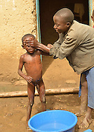 A girl bucket-bathing her young brother in a village in  Western Rwanda