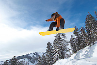 Male snowboarder jumping over snow covered hill mid air