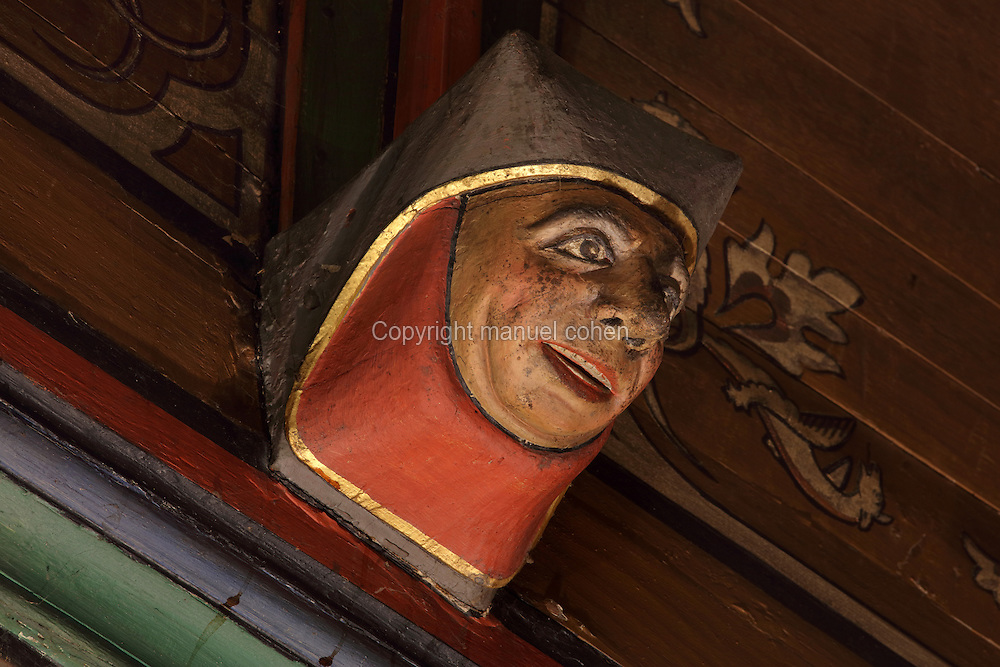 Carved and painted roof bracket with head of a smiling woman, architectural detail of the painted wooden ceiling in the shape of a boat's hull, in the Salle des Povres or Room of the Poor, almost 50m long, in Les Hospices de Beaune, or Hotel-Dieu de Beaune, a charitable almshouse and hospital for the poor, built 1443-57 by Flemish architect Jacques Wiscrer, and founded by Nicolas Rolin, chancellor of Burgundy, and his wife Guigone de Salins, in Beaune, Cote d'Or, Burgundy, France. The hospital was run by the nuns of the order of Les Soeurs Hospitalieres de Beaune, and remained a hospital until the 1970s. The building now houses the Musee de l'Histoire de la Medecine, or Museum of the History of Medicine, and is listed as a historic monument. Picture by Manuel Cohen
