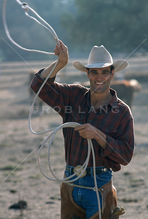 cowboy walking on a ranch while using a lasso