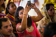 "15 SEPTEMBER 2013 - BANGKOK, THAILAND: A Hindu woman photographs services with her iPhone on the last day of Ganesha Chaturthi celebrations at Shiva Temple in Bangkok. Ganesha Chaturthi is the Hindu festival celebrated on the day of the re-birth of Lord Ganesha, the son of Shiva and Parvati. The festival, also known as Ganeshotsav (""Festival of Ganesha"") is observed in the Hindu calendar month of Bhaadrapada. The festival lasts for 10 days, ending on Anant Chaturdashi. Ganesha is a widely worshipped Hindu deity and is revered by many Thai Buddhists. Ganesha is widely revered as the remover of obstacles, the patron of arts and sciences and the deva of intellect and wisdom. The last day of the festival is marked by the immersion of the deity, which symbolizes the cycle of creation and dissolution in nature. In Bangkok, the deity (statue) was submerged in the Chao Phraya River.     PHOTO BY JACK KURTZ"