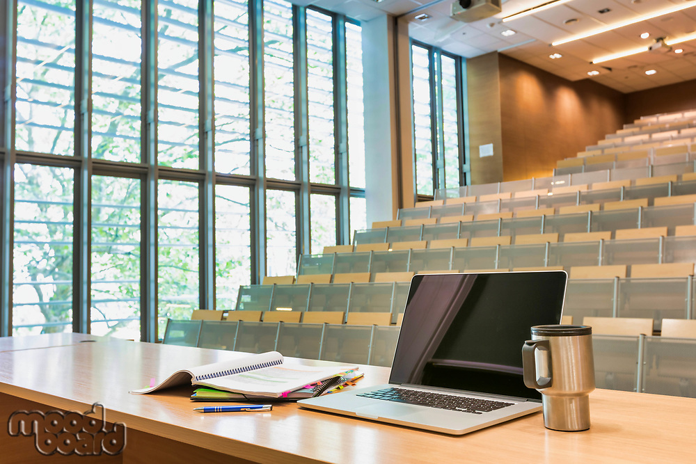 Photo of laptop on professor desk with tumbler in classroom
