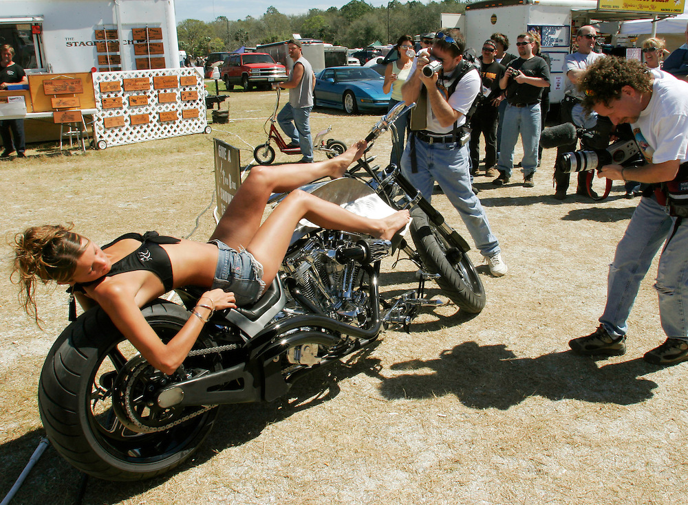 Jeney Regelean attracts attention as she lies on a custom chopper by Finish Line cycles at the Cabbage Patch bar during a Bike Week event in Samsula, Florida March 8, 2005.  Daytona Beach, Florida and the surrounding area host the annual Bike Week ten-day event attracting motorcyclists of all varieties with over 500,000 expected this year.