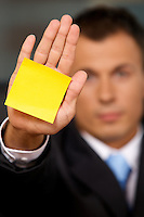 Businessman in office with blank adhesive note stuck to his hand