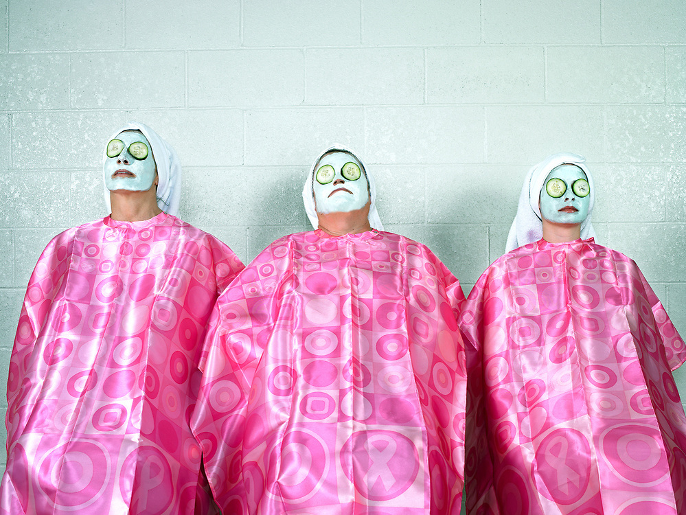 Three women ages 30 -60 sitting in gowns with cream on faces and cucumbers covering eyes  at spa.