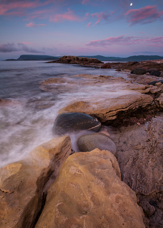 Colorful clouds light up at sunset as the moon sets along the rocky coastline of Cape Breton island, Nova Scotia, Canada