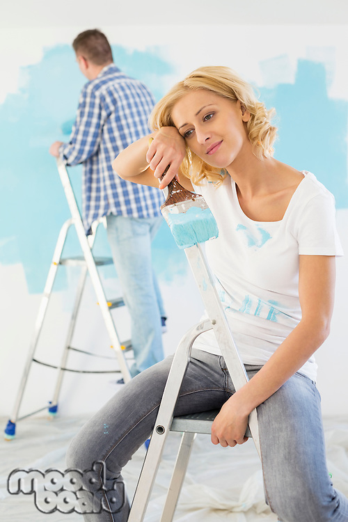 Tired woman holding paintbrush with man painting in background