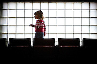 """JEROME A. POLLOS/Press..Hanna Christensen, 3, plays in front of the glass-block window Saturday near the """"nose bleed"""" seats at North Idaho College's Rolly Williams Court during the Idaho All-Star basketball games."""
