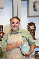 Portrait of a happy potter holding ceramic pot in artist's studio