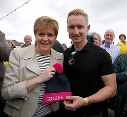 First Minister in Oban to visit SNP street stall and walkabout, George St, Oban..Pictured here receiving an Oban Live hat from Daniel Gillespie of Skerryvore...... <br /> (c) Stephen Lawson | Edinburgh Elite media