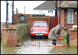 A residents in Egham, United Kingdom, builds a flood defence wall outside her house as the town is hit by floods, Wednesday, 12th February 2014. Picture by Andrew Parsons / i-Images