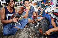 Men sitting outside the large tent where the cockfightings are taking place.<br />