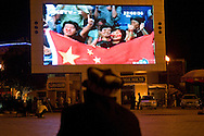 In Kashgar on the square next to the Id Kah mosque, a Uyghur is watching a news segment featuring a Chinese crowd waving a Chinese flag.