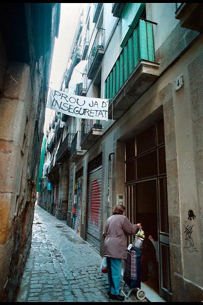 Spanje, barcelona, 10-1-2004..Waarschuwing, protest tegen de onveiligheid op straat, in het centrum van de stad. Vrouw met boodschappen voor haar huis. Straatbeeld,stadsbeeld, nauw straatje. Woonomstandigheden..Foto: Flip Franssen
