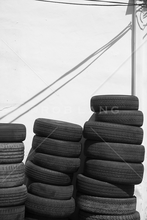 old tires piled up against a white wall