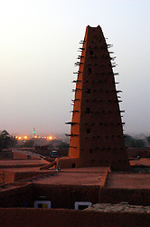 "Niger,Agadez,2007. The distinctive Sahel architecture of the ""Grand Mosquee"" of Agadez at twilight. With the exception of modern antennas, minarets are the tallest structures in the city."