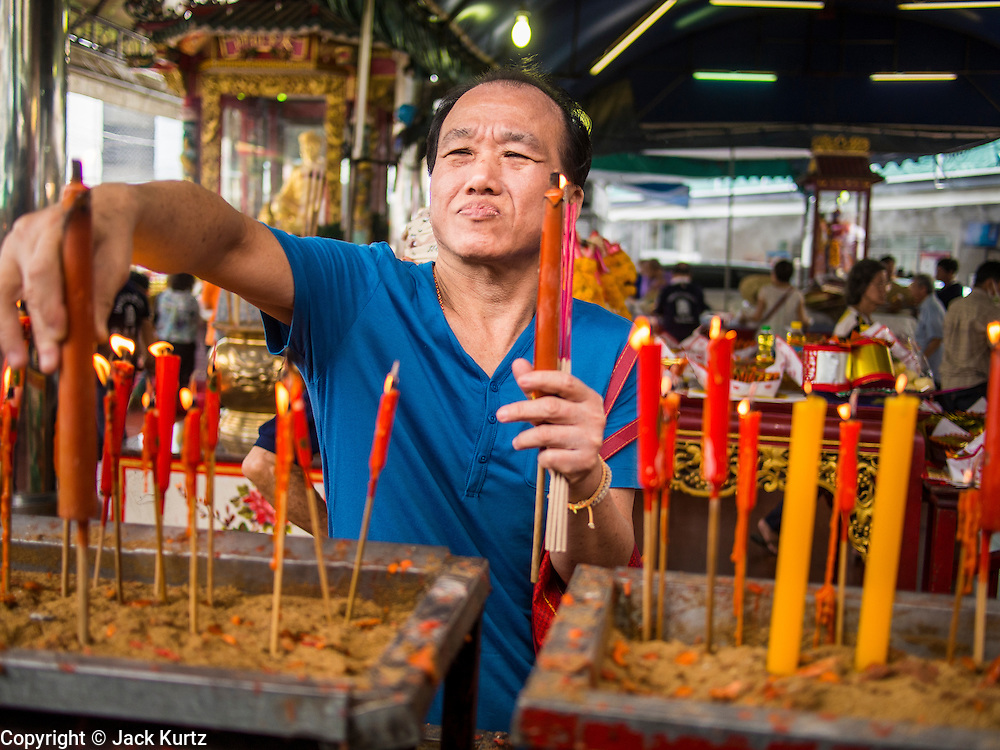 "26 AUGUST 2013 - BANGKOK, THAILAND: A man lights candles and pray at the Poh Teck Tung Foundation for Hungry Ghost Month in Bangkok. Poh Teck Tung operates hospitals and schools and provides assistance to the poor in Thailand. The seventh lunar month (August - September in 2013) is when the Chinese community believes that hell's gate will open to allow spirits to roam freely in the human world for a month. Many households and temples will hold prayer ceremonies throughout the month-long Hungry Ghost Festival (Phor Thor) to appease the spirits. During the festival, believers will also worship the Tai Su Yeah (King of Hades) in the form of paper effigies which will be ""sent back"" to hell after the effigies are burnt.    PHOTO BY JACK KURTZ"