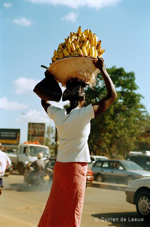 Vrouw draagt bananen in de stad Kampala, hoofdstad van Uganda
