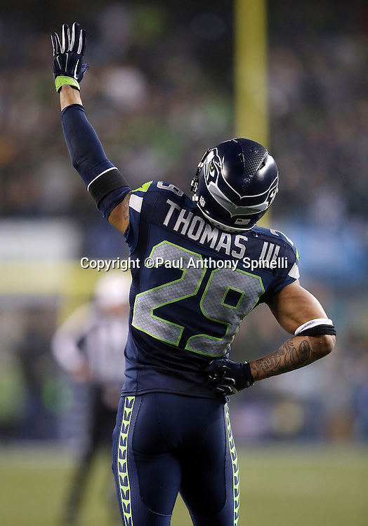 Seattle Seahawks free safety Earl Thomas (29) holds his hand in the air as he celebrates after a pick six interception by Seattle Seahawks strong safety Kam Chancellor (31) for a touchdown and a 31-10 late fourth quarter Seahawks lead during the NFL week 19 NFC Divisional Playoff football game against the Carolina Panthers on Saturday, Jan. 10, 2015 in Seattle. The Seahawks won the game 31-17. ©Paul Anthony Spinelli