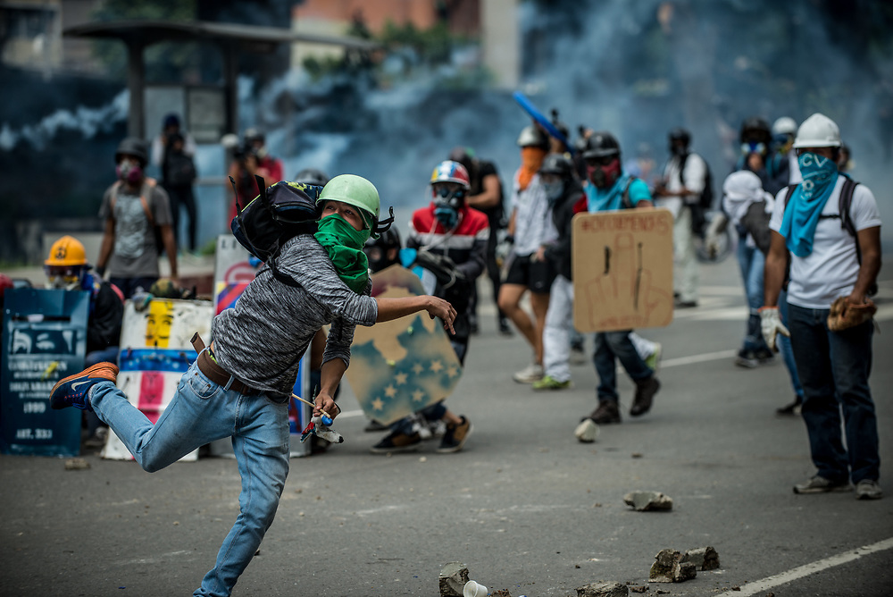 CARACAS, VENEZUELA - MAY 24, 2017:  Anti-government protesters hurl stones and molotov cocktails during clashes with members of the National Police, who responded by heavily tear gassing and firing rubber bullets and buckshot at them. The streets of Caracas and other cities across Venezuela have been filled with tens of thousands of demonstrators for nearly 100 days of massive protests, held since April 1st. Protesters are enraged at the government for becoming an increasingly repressive, authoritarian regime that has delayed elections, used armed government loyalist to threaten dissidents, called for the Constitution to be re-written to favor them, jailed and tortured protesters and members of the political opposition, and whose corruption and failed economic policy has caused the current economic crisis that has led to widespread food and medicine shortages across the country.  Independent local media report nearly 100 people have been killed during protests and protest-related riots and looting.  The government currently only officially reports 75 deaths.  Over 2,000 people have been injured, and over 3,000 protesters have been detained by authorities.  PHOTO: Meridith Kohut