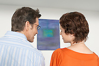 Couple discussing painting in art gallery