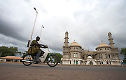 Men riding motorbike by large mosque in Tamale, Ghana on Sunday June 3, 2007.