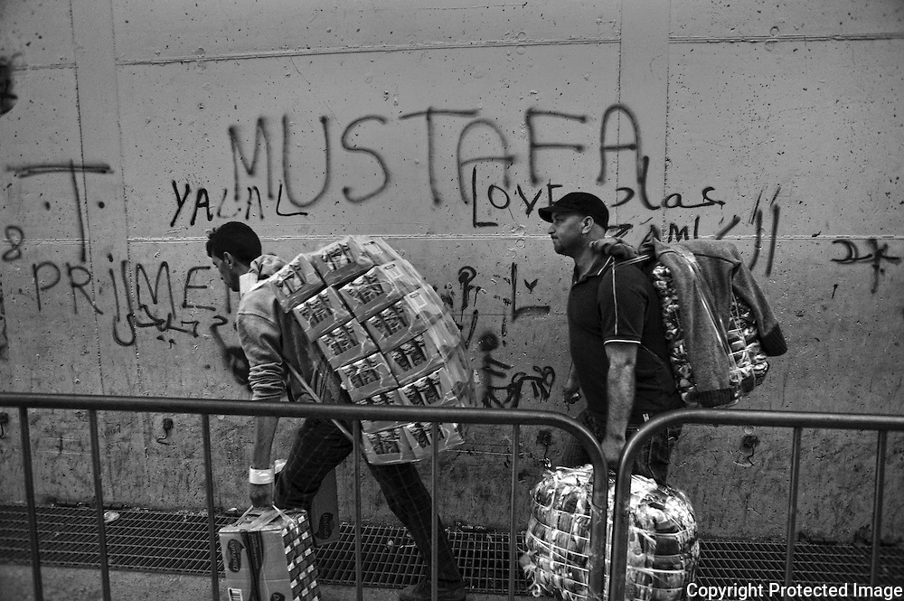 CEUTA, SPAIN - JUNE 27, 2010 :Two man carrying goods from the warehouses located around the pedestrian cross border of El Biutz. Thousands  of people are involved in transporting smuggled goods from Ceuta (an Spanish enclave on the North African coast) to Morocco, it is estimated that every day enter 10.000 porters, mostly women, that it make between three and five trips to Morocco with all types of products purchased on  the warehouse border area of El  Biutz in Ceuta, Spain .( Photo by Jordi Cami )
