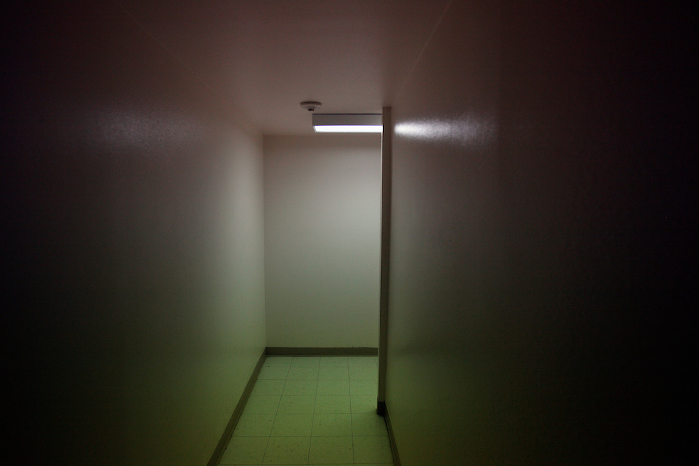 An interior hallway, lit by one fluorescent light.