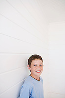 Young boy standing against weather boarded wall portrait