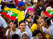 29 NOVEMBER 2017 - YANGON, MYANMAR: People wave Vatican and Myanmar flags before the Papal Mass in Yangon. Hundreds of thousands of Catholics from Myanmar attended the mass said by Pope Francis at Kyaikkasan Sports Ground in Yangon Wednesday. Pope Francis is on the first visit by a Pope to Myanmar.  PHOTO BY JACK KURTZ