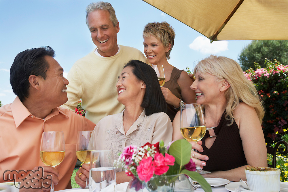 Five friends at table drinking wine at garden party