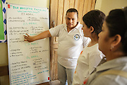 Sabin Institute senior program officer Karen Palacio, (center) listens to a health worker tell her about an ongoing vaccination campaign at the health center in San Esteban, Honduras on Thursday April 25, 2013.