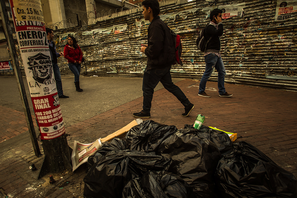 Bogotá, Colombia - January 24, 2014:  People walk past trash piled on the curb in downtown Bogotá. Mayor Gustavo Petro is currently appealing a decision by the inspector general to remove him from office for failure to correctly run the city's waste management program. Petro, a former left-wing M-19 guerrilla says the decision is politically motivated.  Thousands of outraged Petro supporters have recently held protests in Bolívar Square to show their support of the mayor.  CREDIT: Meridith Kohut for The New York Times