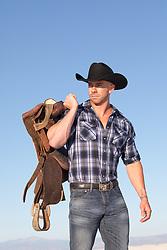 muscular cowboy holding a saddle
