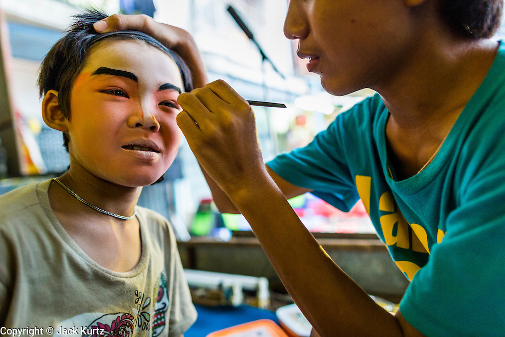 27 APRIL 2013 - BANGKOK, THAILAND: Children who perform in a Chinese opera put on their makeup before a performance. Chinese opera is a family endeavor and many times children grow up performing alongside their parents. Chinese opera was once very popular in Thailand and is usually performed in the Teochew language. Millions of Chinese emigrated to Thailand (then Siam) in the 18th and 19th centuries and brought their cultural practices with them. Recently its popularity has faded as people turn to performances of opera on DVD or movies. There are as many 30 Chinese opera troupes left in Bangkok. They travel from Chinese temple to Chinese temple performing on stages they put up in streets near the temple, sometimes sleeping on hammocks they sling under their stage. The opera troupes are paid by the temple, usually $700 to $1000 a night.   PHOTO BY JACK KURTZ