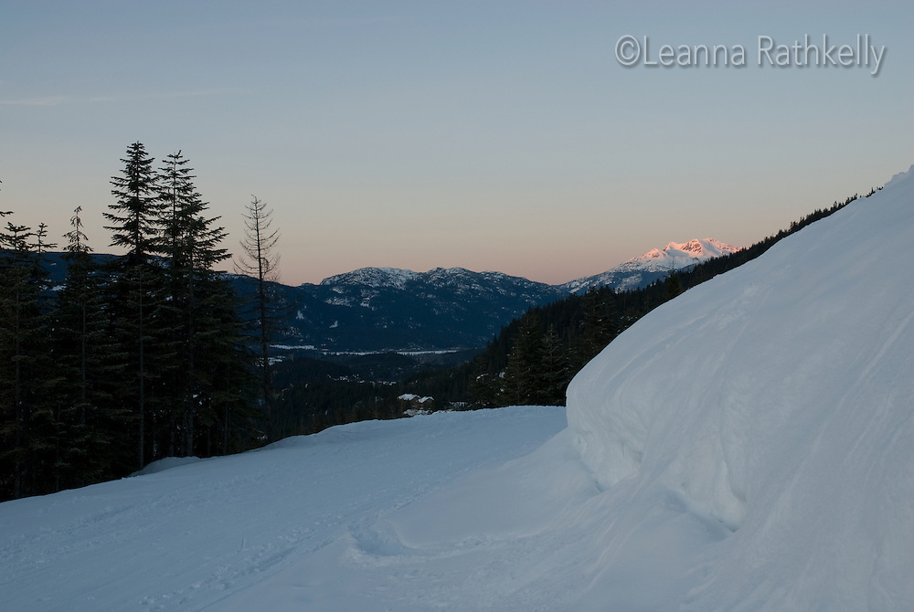 Rainbow and Sproat Mountains darken as the sun sets over the Whistler Valley in winter.