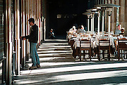 Spanje, Barcelona, 10-1-2004..Bewoner van de Plaza Reial, bij de Ramblas, opent zijn deur. Mensen eten buiten een maaltijd, lunch. Plein, gallerij, toerisme, stadsbeeld..Foto: Flip Franssen