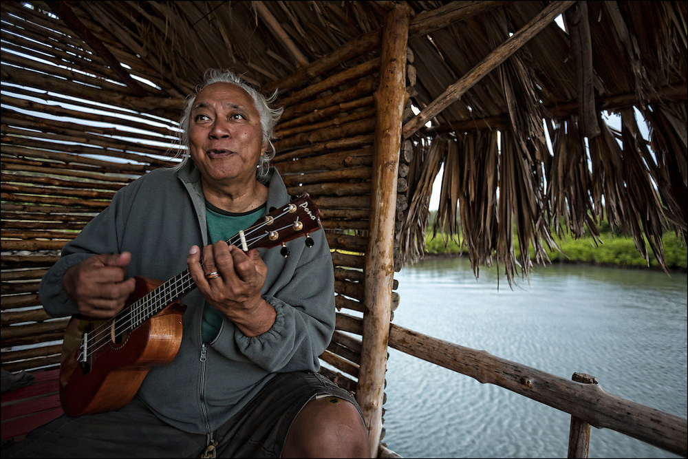 """Brother Nolan also referred to as """"Uncle No"""" plays ukulele during sunset kanikapila at the Ho'ea Initiative base camp located at the Keawanui Fishpond on Molokai."""