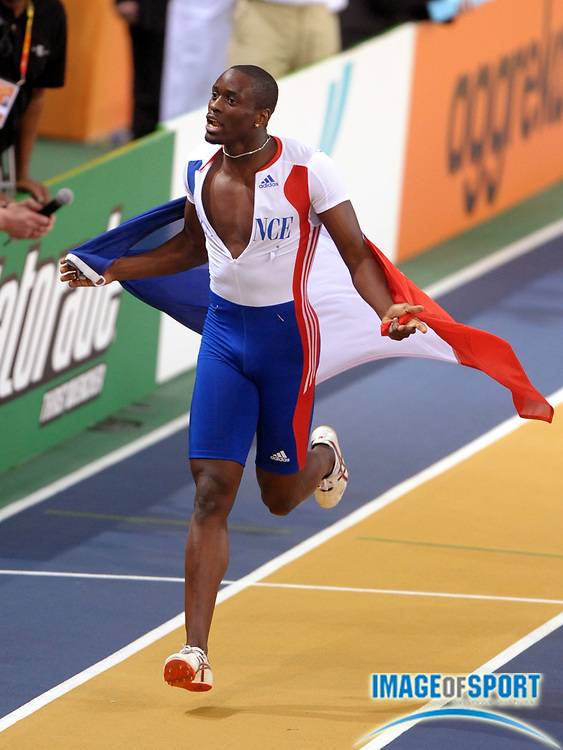 Mar 14, 2010; Doha, QATAR; Teddy Tamgho (FRA) takes a victory lap after setting a world record of 58-8 3/4 (17.90m) in the triple jump in the IAAF World Indoor Championships at the Aspire Dome.