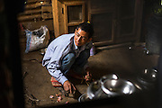 Ratna Baniya (28) cooks lunch in their temporary home in Chautara, Sindhupalchowk, Nepal on 29 June 2015. His three daughters lost their mother during the April 25th earthquake that completely levelled their house. His 2nd daughter Aastha was buried under the rubble together with her mother but Aastha survived. As he cannot care for the children on his own, SOS Childrens Villages has since been supporting the grandmother with financial and social support so that she can manage to raise the children comfortably and ensure that they will all be schooled. Photo by Suzanne Lee for SOS Children's Villages