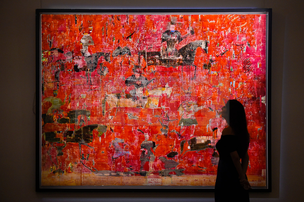 """© Licensed to London News Pictures. 18/10/2019. LONDON, UK. A staff member poses with """"Hunting Red No. IV"""" by Reza Derakshani (Est. GBP50,000-70,000).  Preview of Islamic, Indian and Middle Eastern art to be auctioned at Sotheby's, New Bond Street, on 22 and 23 October.  Photo credit: Stephen Chung/LNP"""