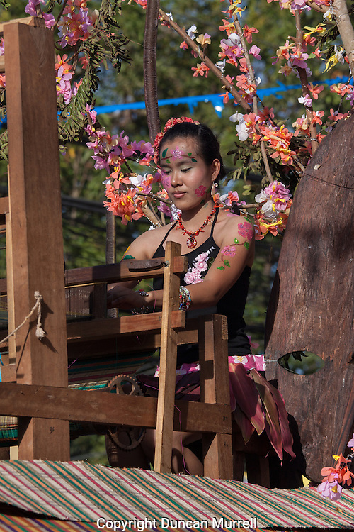 Woman weaving on a float during the Balayong Festival. The festival at the beginning of March commemorates the founding anniversary of the City of Puerto Princesa, Palawan, highlighted by balayong tree-planting, street dancing and a colourful floral parade depicting the Palawan cherry blossoms from which the festival derives its name. The Palawan cherry is one of the most popular flowering trees in Palawan and known by the locals as the Balayong, a beautiful tree that when it is in full bloom resembles the cherry blossoms of Japan.