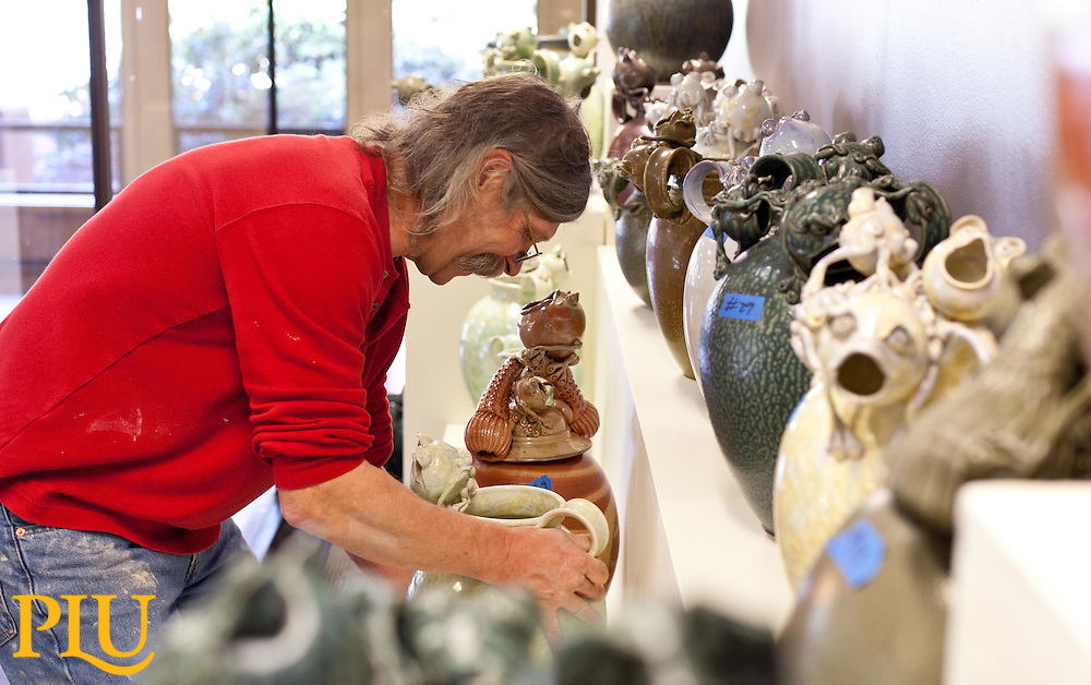 Steve Sobeck positioning his frog sculptures in place. (Photo/John Froschauer)