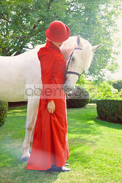 Woman in Red Equestrian Outfit Standing in Garden with Horse