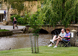 © Licensed to London News Pictures.14/06/2012. Bourton-0n-the-Water, UK. Summers here, tourists flock to the Costswolds to enjoy a British summer. Pictured, a couple take time out to enjoy the sun on the village green in Bourton-on-the-Water.Photo credit : Dave Warren/LNP