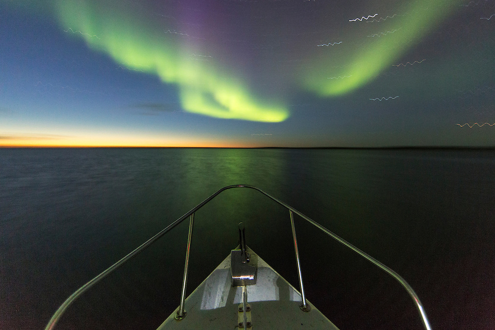 Canada, Nunavut, Territory, Aurora borealis glows in night sky above C-Dory expedition boat in Roes Welcome Sound in northern Hudson Bay